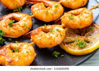 Grilled tiger shrimps skewers with lemon - seafood style