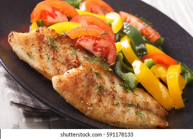 Grilled tilapia fillets and fresh vegetable salad on a plate close-up. horizontal