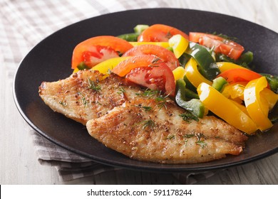 Grilled tilapia steak and fresh vegetable salad on a plate close-up. horizontal