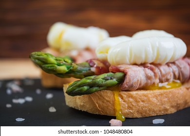 Grilled toast with asparagus in bacon and poached egg on wooden background