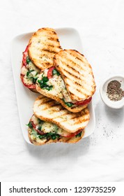 Grilled tomatoes, spinach and mozzarella sandwiches - healthy breakfast, snack, tapas, appetizers on a light background, top view