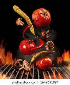Grilled tomatoes, zucchini, chili, champignons, halves of garlic are falling down on black background. Barbecue, fire, charcoal and smoke. Close up
