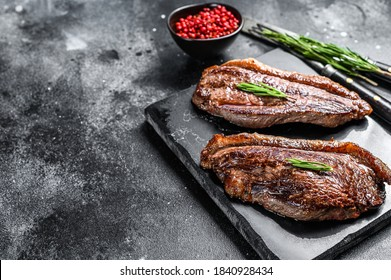 Grilled top sirloin cap or picanha steak on a stone chopping Board. Black background. Top view. Copy space