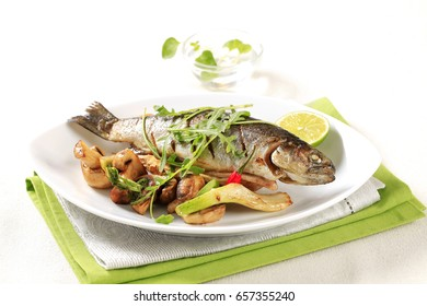 Grilled trout served with button mushrooms