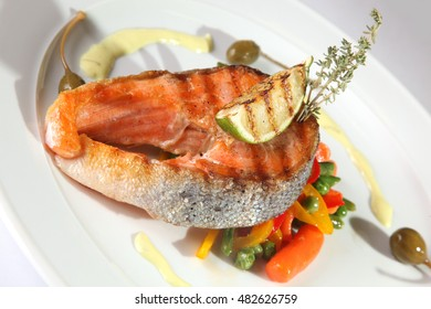 Grilled trout with vegetables and baked lime on plate