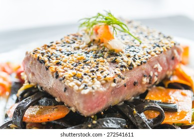 Grilled Tuna fish meat steak with black spaghetti - soft focus point
