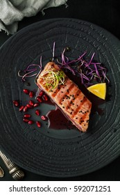 Grilled tuna with spices, sauce and sesame seeds on a plate on a dark background