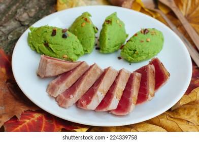 Grilled tuna steak and mashed green peas