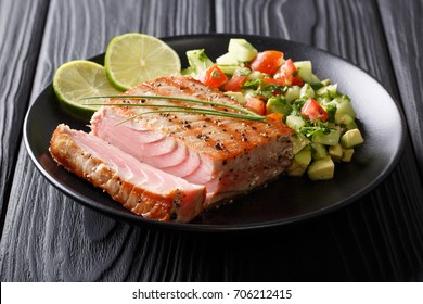 Grilled tuna steak with pepper and avocado cucumber salsa close-up on a plate. horizontal