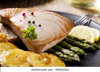 Grilled tuna steak served on asparagus with roasted potatoes on a black plate.