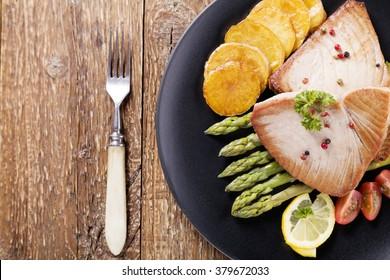 Grilled tuna steak served on asparagus with roasted zmieniakami on a black plate.