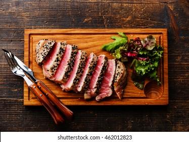 Grilled Tuna steak in sesame and Green salad on wooden board on dark wooden background