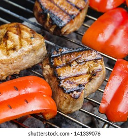 Grilled tuna steaks and cut red bell pepper on grill