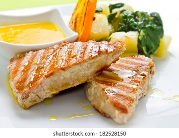Grilled Tuna steaks served with boiled potato and lemon sauce, garnished with tomato and orange