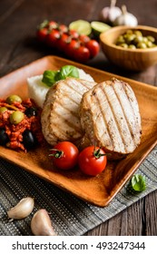 Grilled tuna steaks served with rice, tomato sauce with olives