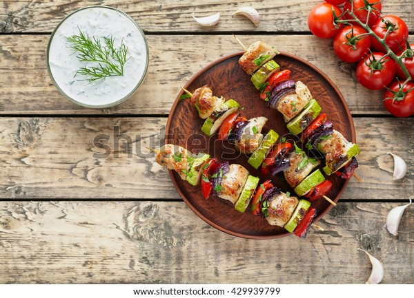 Grilled turkey or chicken meat shish kebab skewers with tzatziki sauce, chopped parsley, garlic and tomatoes on rustic wooden table background. Traditional barbecue grill food