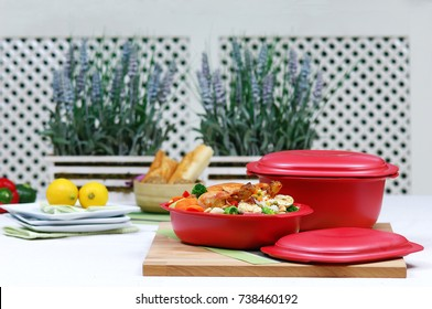 Grilled turkey with vegetables in a red storage box, another box next to it, lemons and plates on the left side, ericas on the background, kitchen table, christmas kitchen