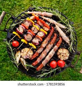 Grillades, saucisses, brochettes de légumes et de viandes avec herbes sur grill en fer forgé, vue de dessus
