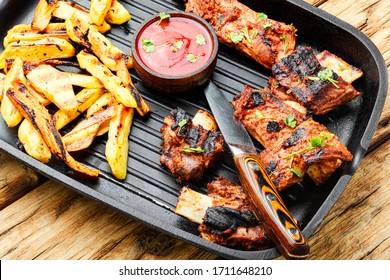 Grilled veal ribs with fried potatoes in a grill pan.Barbecue ribs with french fries