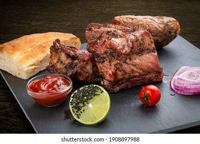 Grilled veal steak with baked potatoes, matnakash and red sauce. Served on a stone plate