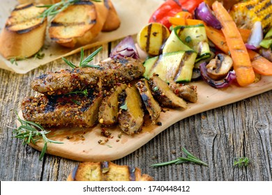 Grilled vegan seitan steaks with mixed vegetables and crusty baguette