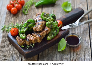 Grilled vegan seitan steaks with pimientos de padron and served with a herb soy sauce on a rustic wooden background