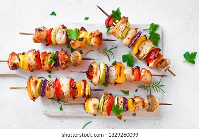 Grilled vegetable and chicken skewers with  bell peppers, zucchini, onion and mushrooms on white background, top view. Meat and vegetables kebabs on skewers.