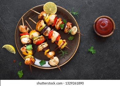 Grilled vegetable and chicken skewers with  bell peppers, zucchini, onion and mushrooms on black background, top view. Meat and vegetables kebabs on skewers.