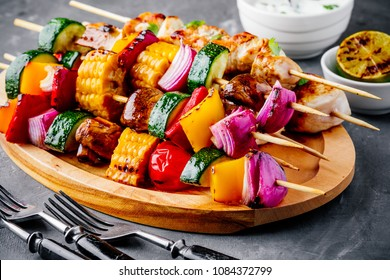 Grilled vegetable and chicken skewers with sweet corn, paprika, zucchini, onion, tomato and mushroom on a wooden plate