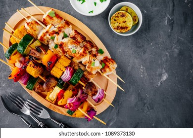 Grilled vegetable and chicken skewers with sweet corn, paprika, zucchini, onion, tomato and mushroom on a wooden plate, top view