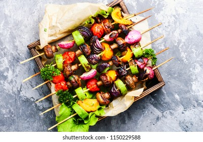 Grilled vegetable kebabs on skewers with tomato, pepper, mushrooms,zucchini and onion.Diet barbecue.Vegan skewers
