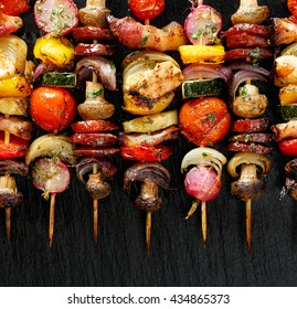 Grilled vegetable and meat skewers  on the black stone background, top view