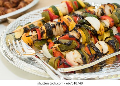 Grilled vegetable skewers with zucchini squash, summer squash, onions, red peppers and yellow peppers.