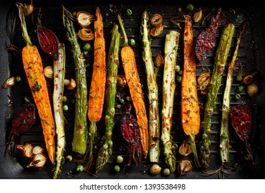 Grilled vegetables  with the addition of olive oil, herbs and spices  on the grill plate, top view. Healthy nutrition concept, vegan meal