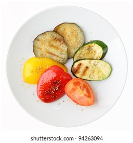 Grilled vegetables of different colors on white round dish isolated on a white background