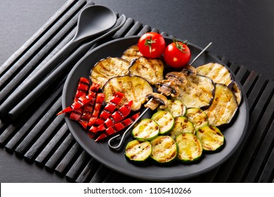 Grilled vegetables: eggplant, zucchini, pepper. Skewer with mushrooms. On a black plate and a black background.
