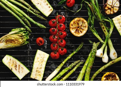 Grilled vegetables green asparagus, garlic, lemon, spring onion, zucchini, cherry tomatoes, salad on bbq grill rack over charcoal. Top view. Barbecue concept