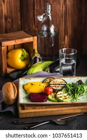 Grilled vegetables, Lenten menu. Close up. Appetizing eggplant, pepper, beetroot, tomato, squash on plate and wooden board. Ingredients and water in glass in background. Healthy rustically lifestyle