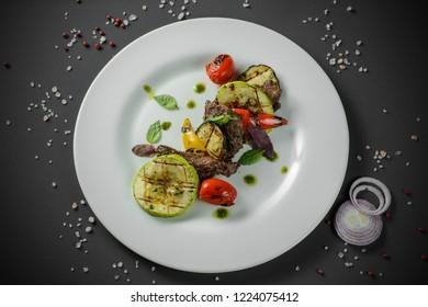 Grilled vegetables with meat decorated on dark background