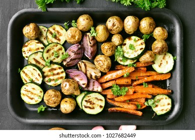 Grilled vegetables on baking tray over dark background. Top view, flat lay