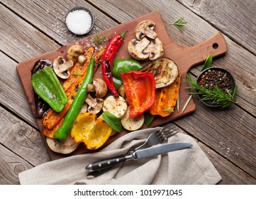 Grilled vegetables on cutting board on wooden table. Top view