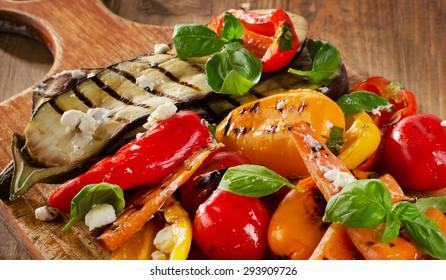 Grilled vegetables on a old wooden board.