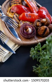 Grilled vegetables on a wooden plateau. Background dark, green flower branches, with a light towel and cutlery