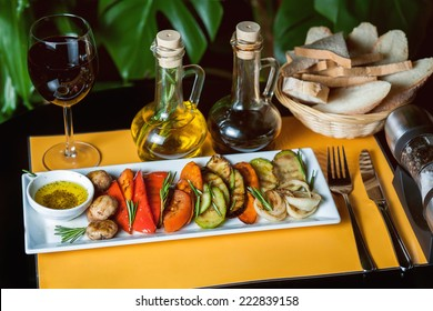 Grilled vegetables on yellow and black background with a glass of wine, oil, vinegar and bread.
