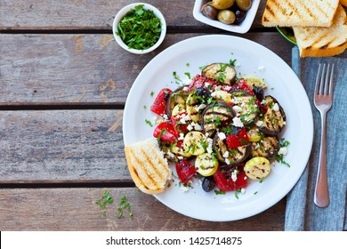 Grilled vegetables salad with feta cheese in white plate on wooden table. Copy space. Top view.