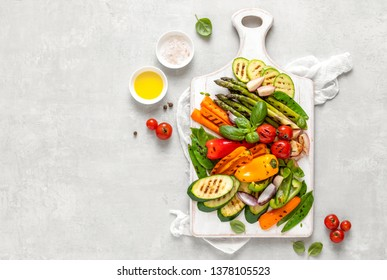 Grilled vegetables served on a wooden board, view from above, culinary background with blank space for a text