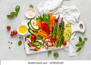 Grilled vegetables served on a wooden board with olive oil and salt, view from above