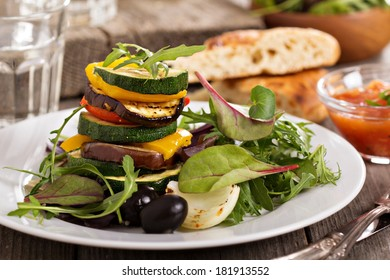 Grilled vegetables stacked on plate with salad leaves