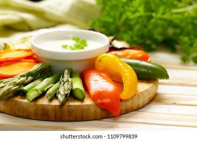 grilled vegetables with yoghurt dip on wooden board