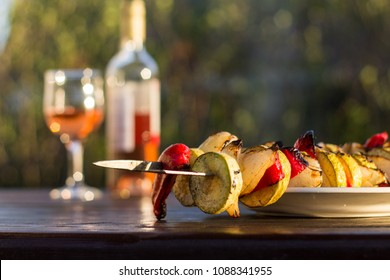 Grilled veggies, vegetable kebab with zucchini, onions and sweet red peppers cooked outdoors on a wooden table in the backyard garden patio, rose wine bottle and glass, harvest, farm
